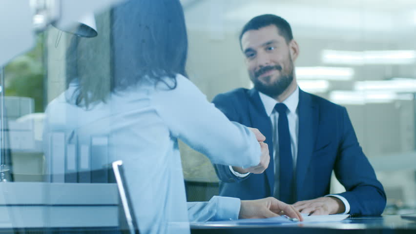 In the Office Businesswoman and Businessman Have Conversation, Negotianing, Draw up a Contract, Sign Documents, Finish Transaction, Shake Hands. Stylish People in Modern Conference Room. 4K UHD.