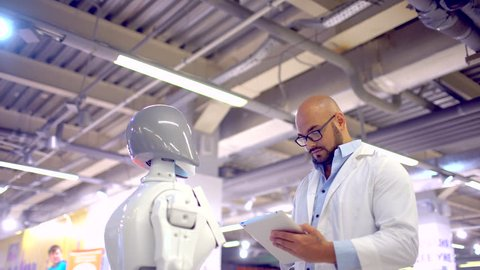 A scientist man and a robot. people human Electronics engineer, scientist inventor in white coat. Control robot using tablet computer. Robot training. person controls the robot. Build robots customize