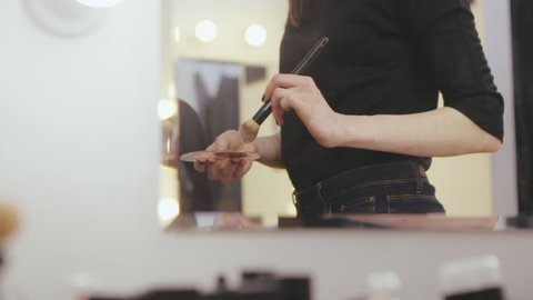 Fashion stylist applying tone cream with makeup brush on skin face woman model front makeup mirror in beauty studio. Professional makeup for actresses before photo session