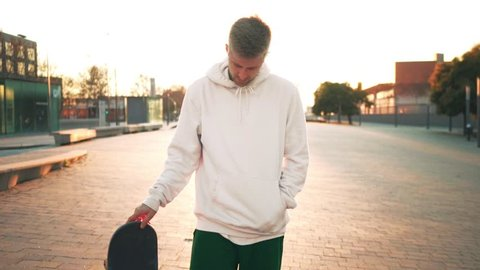 Cinemagraph of trendy hipster or millennial man or teenager stand in sunset light with skateboard and twist in his hand his board, concept cool lifestyle, forever young teen spirit