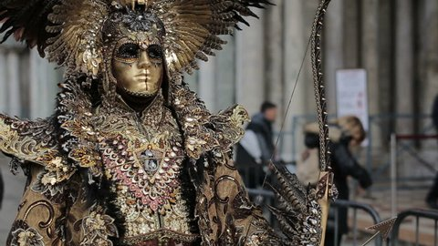 Unidentified people in carnival costumes pose at Venice carnival