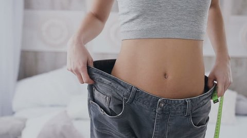 Close-up. A slim girl is measuring her waist with a meter tape. She is also checking how much her jeans are loose after she has lost a bit of weight slow motion