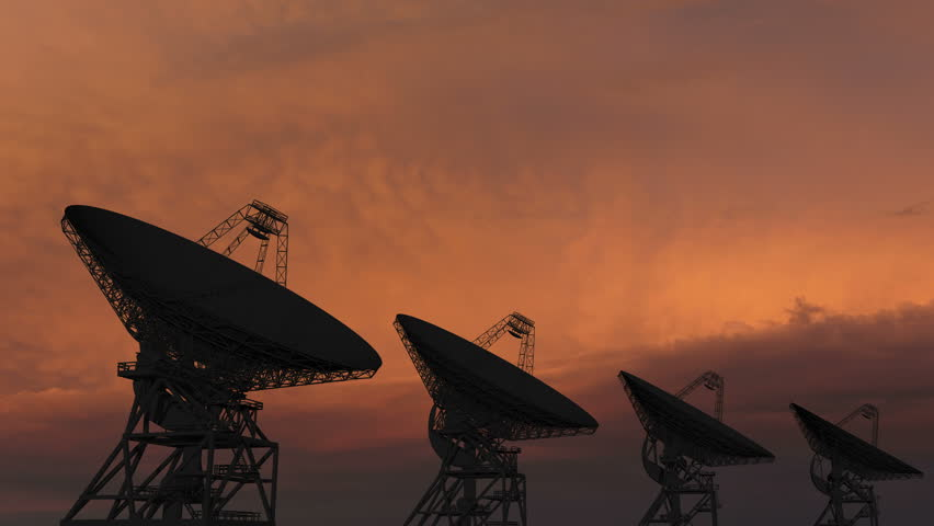 Satellite dishes moving in time-lapse against a sunset sky.