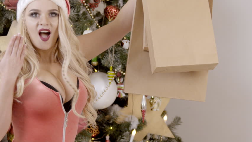 Beautiful blonde is posing with gifts near Christmas tree indoors. Sexual snow maiden is standing near New Year fir in room, holding presents. Young woman dressed in bodysuit with sexy neckline