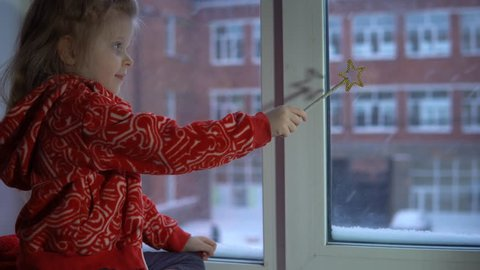 A little pretty girl in a red fleece sweatshirt sits on the windowsill looking at the snowy cityscape. The child waves with a magic wand.