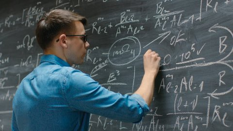 Brilliant Young Academic Finishes Writing Big and Complex Mathematical Formula/ Equation on the Blackboard. Shot on RED EPIC-W 8K Helium Cinema Camera.