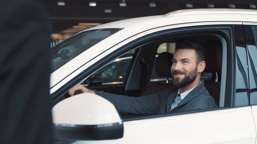 Guy in casual clothes opening car door and sitting on driver's seat. Seller giving keys. Young confident man with beard chewing gum, turning on light in car's interior.   Shutterstock HD Video #1008068083