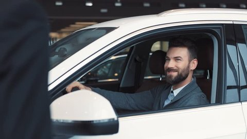 Guy in casual clothes opening car door and sitting on driver's seat. Seller giving keys. Young confident man with beard chewing gum, turning on light in car's interior.