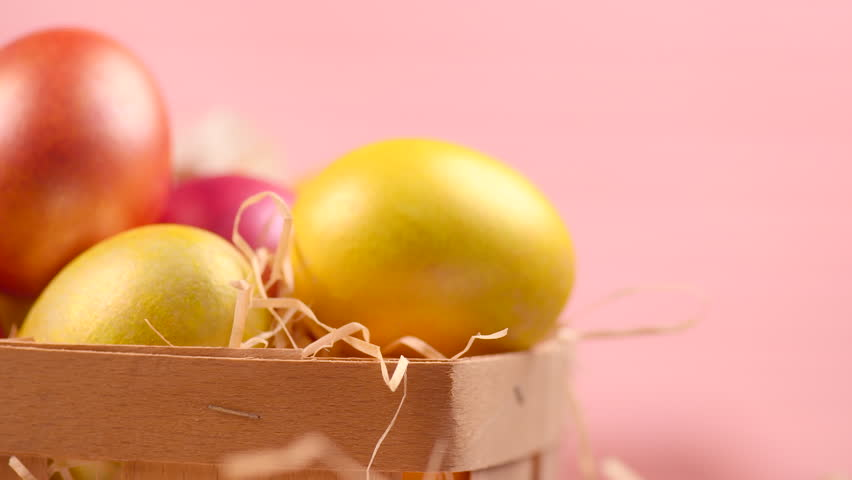 Easter Eggs and spring flowers in a basket on a table over pink background. Rotated Beautiful colorful eggs decorated and painted. Spring Holidays border art design 4K UHD video 3840X2160