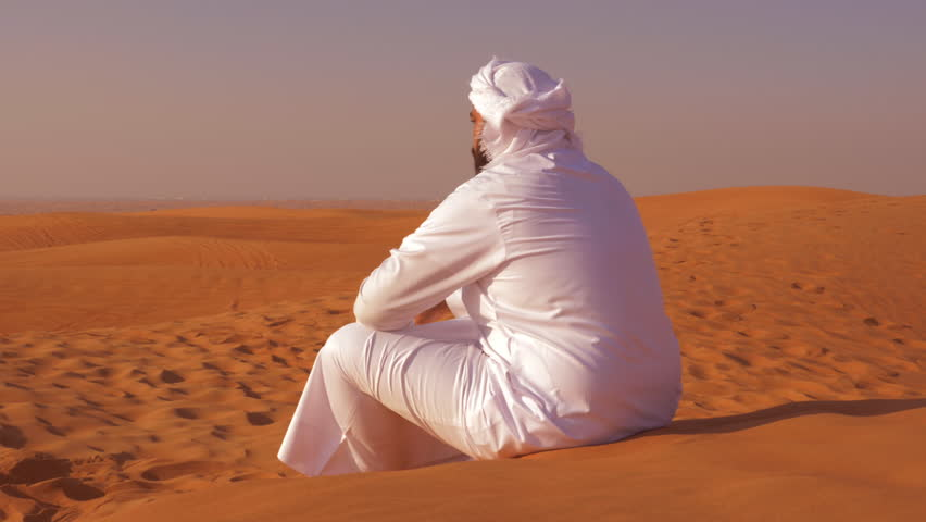 Bedouin man sitting on yellow sand and looking at wild desert back view