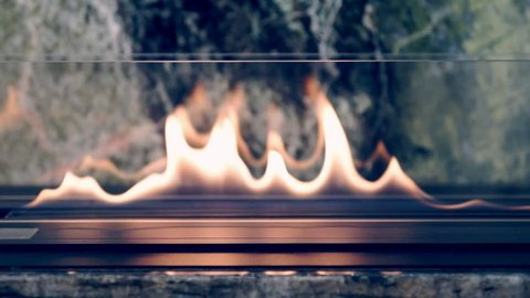 Burning luxury modern gas fireplace with glass media reflecting the flames