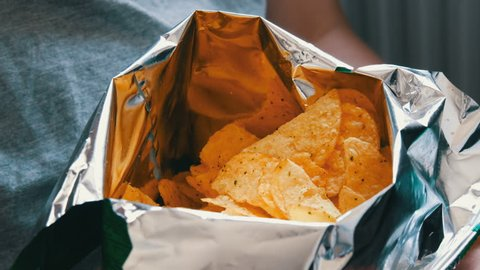 Teenager takes with hands potato chips in packs