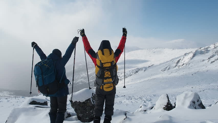 Young Active Successful People Raising Hands On Mountain Top. Hikers Couple with arms raised on top of mountain. Hikers lifting arms up enjoying nature vacation travel adventure. Winter Snow Extreme