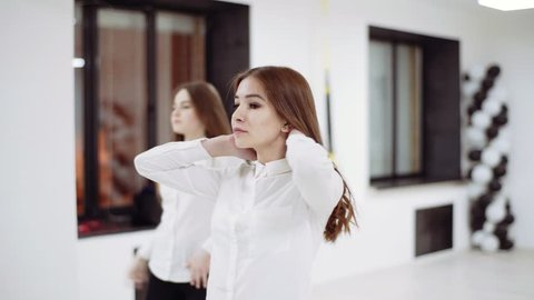 Two girls in white blouses and black trousers dance in front of the mirror.