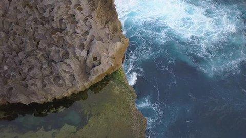 Angels Billabong Natural Pool. Big Blue Sea Waves Crashing on Rock Cliff at Tropical Island. 4K Travel Footage. Nusa Penida, Bali, Indonesia.