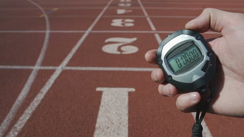 Male hand turning on stopwatch to record time during sport competition, deadline