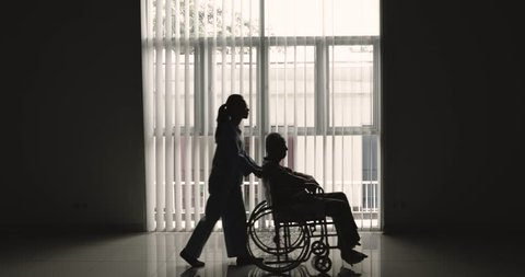 Silhouette of elderly man sitting on wheelchair and pushed by his nurse near the window at home. Shot in 4k resolution