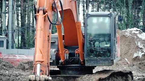 Loader backhoe, excavator digging a trench. Clip. Work of excavating machine on building construction site. Excavator digs a hole