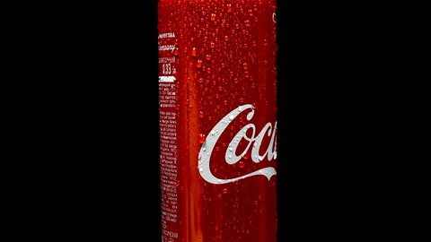 MOSCOW, RUSSIA - MARCH, 2018: Coca-Cola can rotating on black background. Coca-Cola is a carbonated soft drink produced by The Coca-Cola Company - American multinational beverage corporation.
