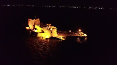 Aerial drone night video from picturesque and famous venetian fortress and small islet of Bourtzi with views to iconic city of Nafplio former capital of Greece, Argolida, Peloponnese