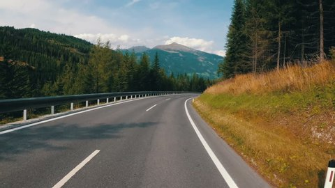 Motorcyclist Rides on a Beautiful Landscape Mountain Road in Austria. First-person view. POV. Viewpoint of a biker riding down a scenic and empty road toward the mountains.