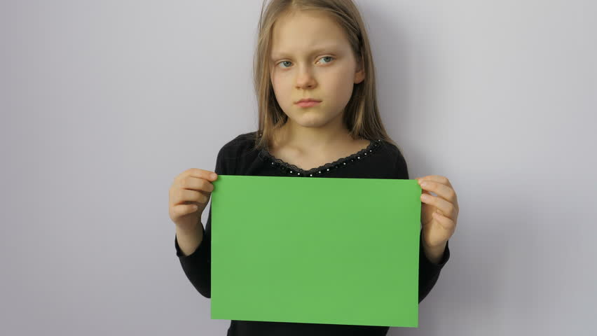 Sad little girl with a green sheet of paper for keying