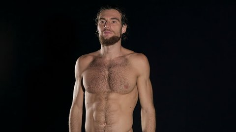 Fitness instructor talking. Half naked fitness trainer man talking in front of camera. With black background.