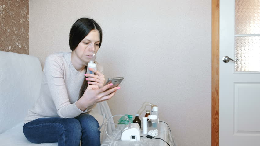 Use nebulizer and inhaler for the treatment. Young woman inhaling through inhaler mask. Side view.