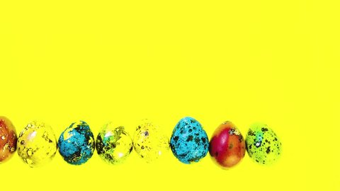 Multicolored beautiful Easter eggs lined in a row on a yellow bright background. Celebratory background for easter. Close-up of Easter eggs.