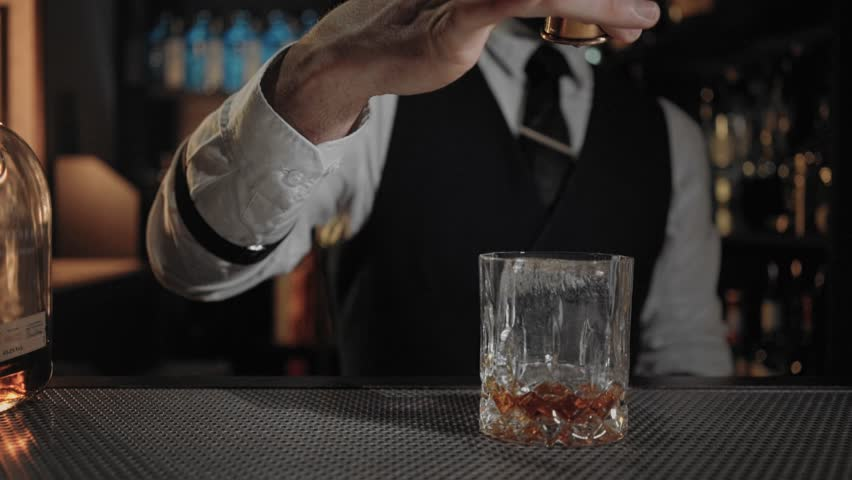 Cinemagraph of professional skilled bartender pour last drops of whiskey or liquor into vintage glass when preparing neat cocktail or drink