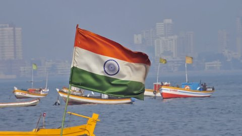 Slow motion shot of a waving Indian flag  installed on one of the fishing boats parked against city skyline, Mumbai, india