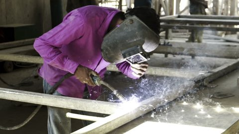 slow motion construction worker welding metal