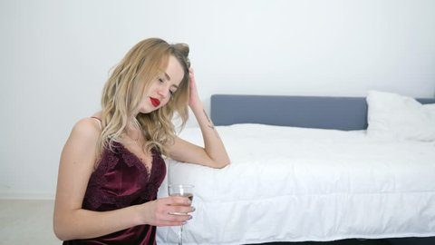 drunk girl in sexy nightdress sit on the floor near the bed with champagne glass in hand