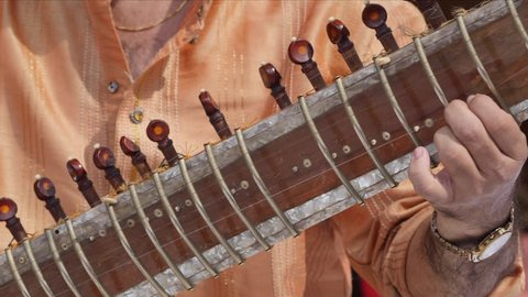 Hands of musician playing instrument Sitar shot in slow motion 180 fps.
