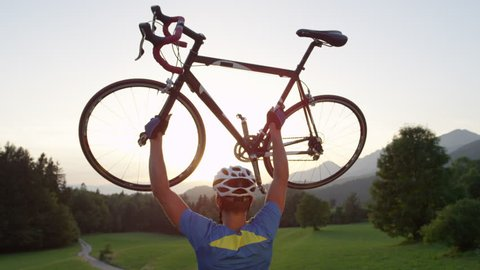 SLOW MOTION, LENS FLARE, CLOSE UP: Thrilled young athlete celebrates win by hoisting his road bicycle. Unrecognizable road cyclist wins race across the sunny countryside and raises his bike over head.