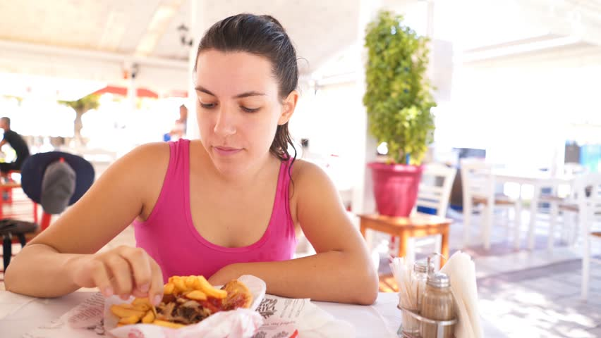 Close up of a young brunette woman eating portion of gyros in a cute, traditional greek tavern, using toothpick