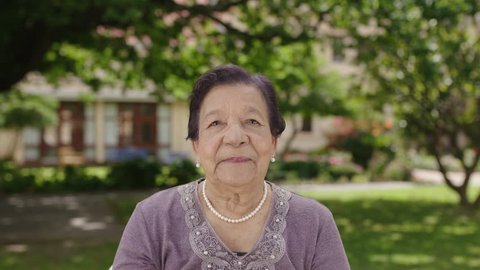 portrait of beautiful elegant elderly woman smiling at camera wearing pearl necklace in garden background retirement home