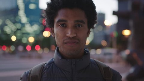 portrait of charming young mixed race man looking pensive at camera serious male in urban evening background real people series