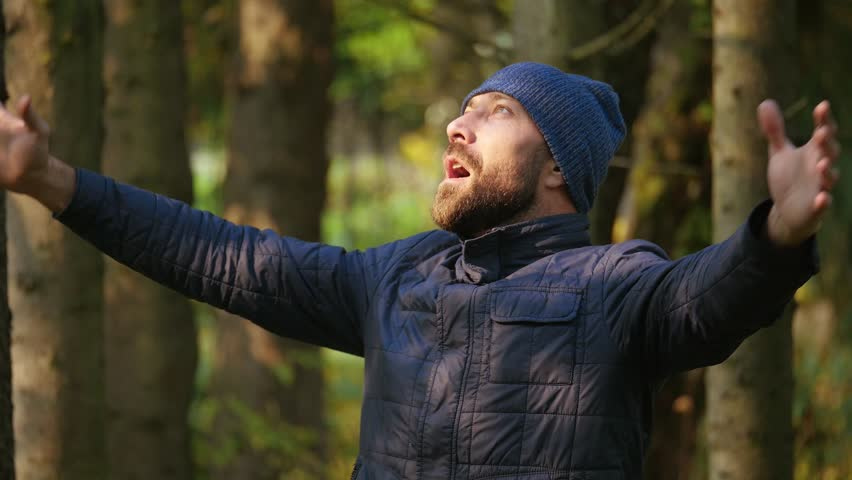 slow motion. Close-up traveler adult bearded man in jacket and knitted hat. emotion brutal guy loudly screaming raising her hands up standing outdoors in nature #1008348463