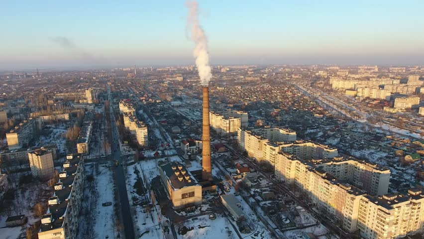 A bird`s eye view of a high cooling tube with dense swhite moke between multistoried buildings at sunset in winter. The drone flies up    Shutterstock HD Video #1008365083