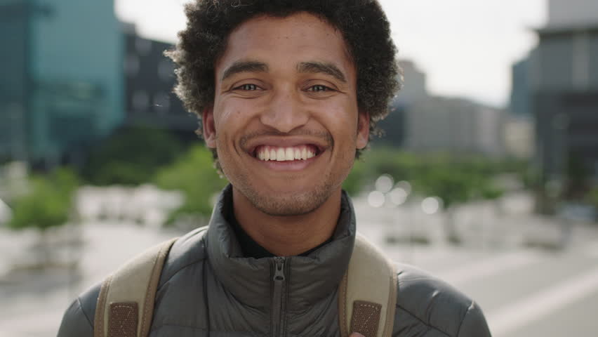 Portrait of handsome young mixed race man laughing cheerful at camera enjoying sunny urban city commuting travel lifestyle | Shutterstock HD Video #1008365533