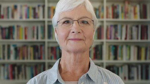close up portrait of elegant middle aged woman teacher smiling happy looking at camera elderly lady wearing glasses in library experience knowledge