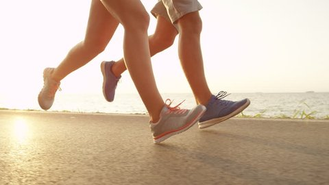 LOW ANGLE, SUN FLARE: Fit young couple runs down sunny asphalt ocean road in the summer. Warm afternoon summer sun illuminating unrecognizable joggers running near the beach in cool sporty sneakers.
