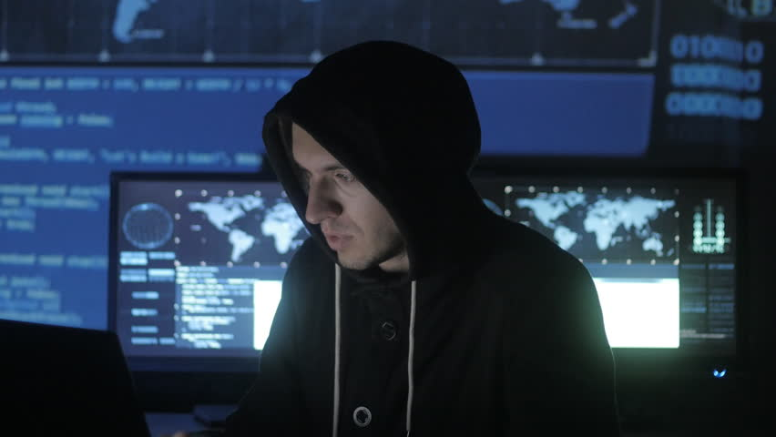 Man geek hacker in hood overworking at computer and suffers from a headache in cyber security center filled with display screens. | Shutterstock HD Video #1008369583