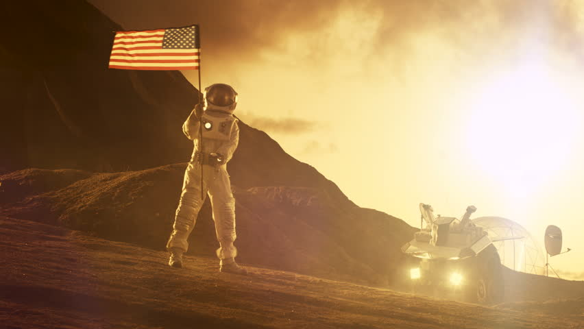 Astronaut Wearing Space Suit Waves American Flag on the Red Planet/ Mars. Patriotic and Proud Moment for the Whole of Humanity. Space Travel and Colonization Concept. Shot on RED EPIC-W 8K Camera.