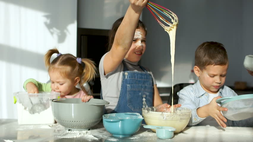 Three children in the kitchen. The girl stirs the dough and watches it flow from the corolla. Mom helps them sift the flour