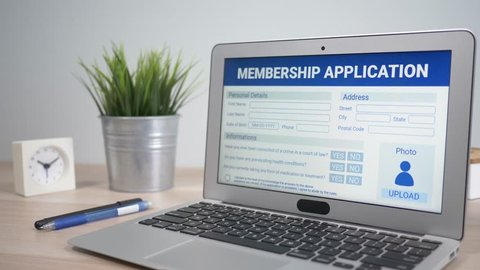 Membership application form concept showing on a laptop computer screen sitting on a desk. Camera is slowly turning around the computer.