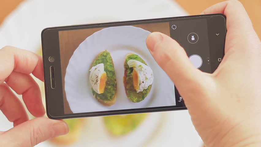 A woman in a restaurant takes a picture of food with a mobile phone camera. Sandwich with poached egg and avocado