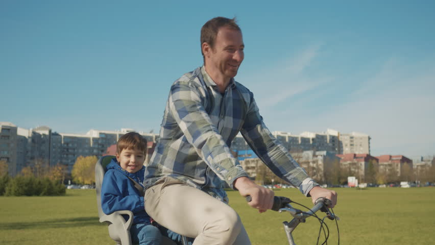 Tracking shot - Father and son spending time together talking on a bicycle ride having fun on a sunny day in the city.