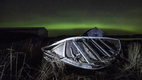 Rotting wooden boat with Northern Lights